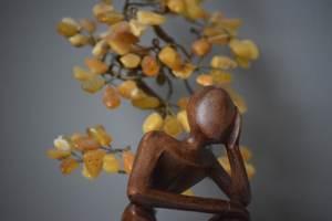 houten beeldje zittend man verhalen infinity uitvaartzorg