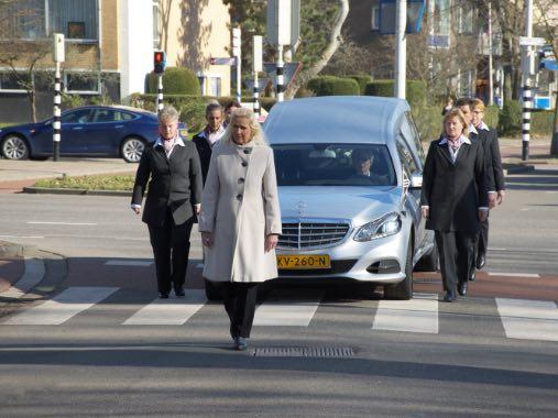 monique kupras loopt voor met de vrouwelijke dragers naast de rouw auto